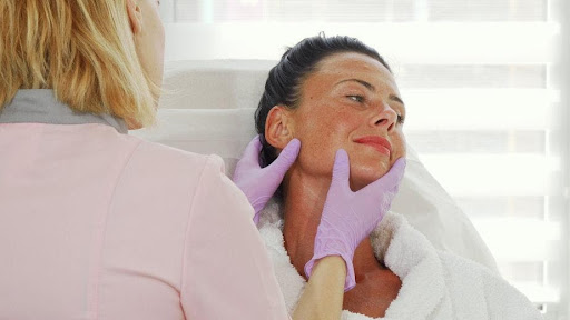 Beautiful mature woman getting her skin examined by professional dermatologist.